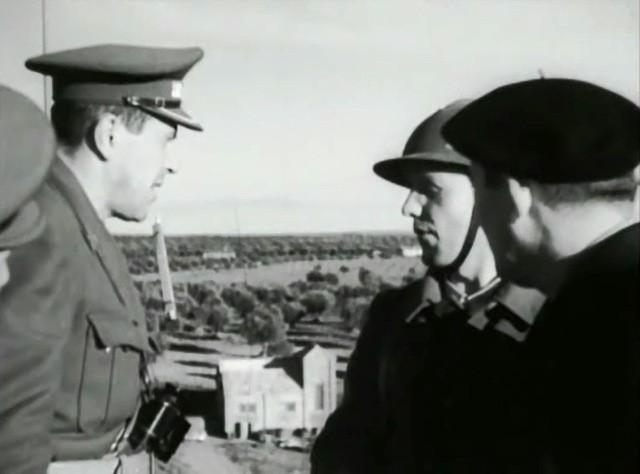 Hans Khale sobre la terraza intermedia de la Casa de la Radio, conversa con el oficial artillero.